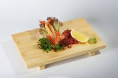 Fresh sashimi. A traditional Japanese delicacy, a portion of fresh sashimi with salad garnish served on a wooden tray Stock Photography