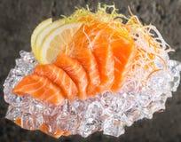 Fresh sashimi on ice. Fresh salmon sashimi on ice over concrete background Royalty Free Stock Photos