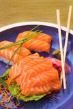 Fresh sashimi and nigiri sushi. Fresh strips of Norwegian salmon Nigiri and rice Sashimi on a blue plate with a bamboo mat in the background and wooden stock photos