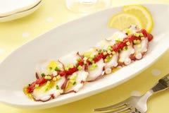 Fresh sashimi of octopus with sauce and onion lemon on white pla. Tter Royalty Free Stock Image