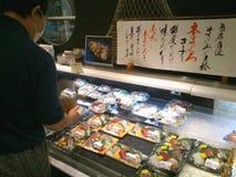Fresh sashimi in retail pack. Kyoto, Japan - May 28, 2015: Customer  shops for fresh sashimi in retail pack at Japanese supermarket. Sashimi is a Japanese Stock Image