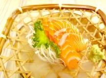 Fresh sashimi salmon with wasabi and lettuce served in a woven rattan dish. Fresh sashimi salmon and wasabi and glass lettuce served in a woven rattan dish stock photos