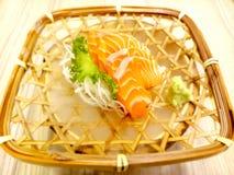 Fresh sashimi salmon with wasabi and lettuce served in a woven rattan dish. Fresh sashimi salmon and wasabi and glass lettuce served in a woven rattan dish stock photography