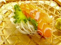 Fresh sashimi salmon with wasabi and lettuce served in a woven rattan dish stock images
