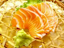 Fresh sashimi salmon with wasabi and lettuce served in a woven rattan dish. Fresh sashimi salmon and wasabi and glass lettuce served in a woven rattan dish royalty free stock photography