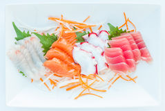 Fresh sashimi set served on white Japanese style plate. Colorful fresh sashimi set served on white japanese style plate royalty free stock photography