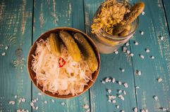 Fresh sauerkraut and pickles. At the turquoise wooden background. Top view. Close-up stock photography