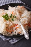 Fresh sauerkraut in a plate close-up vertical. Fresh sauerkraut in a black plate close-up vertical Royalty Free Stock Photo