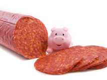 Fresh sausage. Slices of sausage with a  pink pig on the background Royalty Free Stock Images