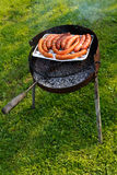 Fresh sausages on a grill outdoor barbecue on the grass background Stock Photo