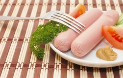 Fresh sausages on a plate Stock Images