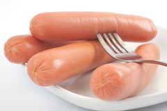 Fresh sausages on a plate. Studio isolated Royalty Free Stock Photos