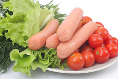 Fresh sausages on a plate with vegetables. Fresh sausages on a plate with with tomatoes and lettuce Stock Images