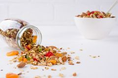 Fresh scattered granola from glass jar on white background. Copy space Stock Photos