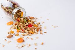 Fresh scattered granola from glass jar on white background. Copy space Royalty Free Stock Photos