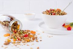 Fresh scattered granola from glass jar on white background. Copy space Royalty Free Stock Image