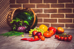 Fresh scattered vegetables and fruits. Overturned basket. Brick wall background. Healthy eating concept. Close-up. Warm toned. Horizontal Royalty Free Stock Photo