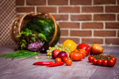 Fresh scattered vegetables and fruits. Overturned basket. Brick wall background. Healthy eating concept. Horizontal Royalty Free Stock Images
