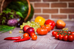 Fresh scattered vegetables and fruits. Overturned basket. Brick wall background. Healthy eatyng concept. Horizontal Royalty Free Stock Image