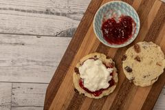 Fresh scone with cream and jam. On wooden chopping board royalty free stock image