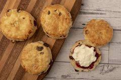 Fresh scones with cream and jam. On wooden background royalty free stock photo