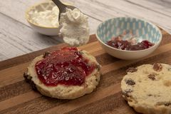 Fresh scones with cream and jam. On table stock photos