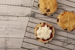 Fresh scones with cream and jam on wire tray. With wooden background royalty free stock photography