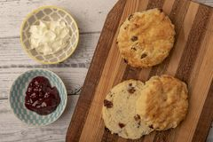 Fresh scones with serving bowls full of jam and cream. On chopping board royalty free stock image