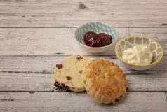 Fresh scones with serving bowls full of jam and cream. On a wooden background stock image