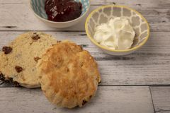 Fresh scones with serving bowls full of jam and cream. On a wooden background royalty free stock images