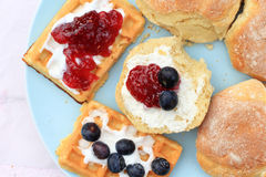 Fresh Scottish scones and belgian waffles with cream and raspberry jam Stock Photos