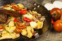 Fresh scrambled egg with ham and chilli peppers on a steel pan. A nourishing traditional breakfast. Calorie meals. Royalty Free Stock Images