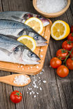 Fresh sea bass on chopping board Stock Images