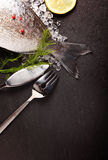 Fresh sea bream on crushed ice. Fresh sea bream fish lying cooling on crushed ice with herbs and spices for cooking and a fish knife and fork arranged on the stock photography