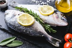 Fresh sea fish on slate board ready for cooking. Fresh sea fish with olive oil, spices and lemon ready for cooking on slate. Closeup view stock images