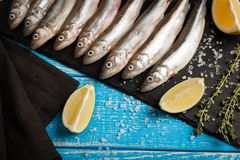 Fresh sea fish smelt or sardines ready for cooking with lemon, thyme, and coarse sea salt on a blue background. The concept of fre. Sh, healthy seafood. Top view Stock Photography