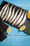 Fresh sea fish smelt or sardines ready for cooking with lemon, thyme, and coarse sea salt on a blue background. The concept of fre. Sh, healthy seafood. Top view Royalty Free Stock Photo