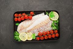 Fresh sea food fish cod white fish before baking on a baking sheet with fresh cherry tomatoes, lemon slices, fresh