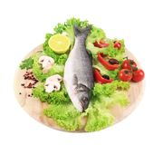 Fresh seabass on platter with lettuce. Isolated on a white background Royalty Free Stock Images
