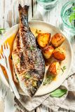 Fresh seabream and potatoes with cherry tomatoes and thyme. On old table stock photography