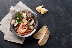 Fresh seafood bowl on stone table. Scallops and shrimps Royalty Free Stock Photos