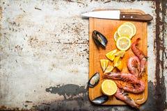 Fresh seafood. Cutting Board with shrimp, shellfish and lemon. Royalty Free Stock Photo