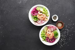 Fresh seafood recipe. Shrimp poke bowl with fresh prawn, brown rice, cucumber, pickled sweet onion, radish, soy beans. Edamame portioned with black and white Stock Images