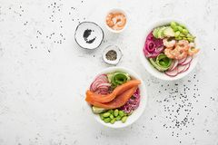 Fresh seafood recipe. Shrimp salmon poke bowl with fresh prawn, brown rice, cucumber, pickled sweet onion, radish, soy Royalty Free Stock Photography