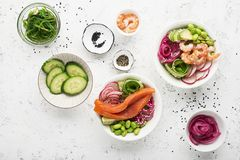 Fresh seafood recipe. Shrimp salmon poke bowl with fresh prawn, brown rice, cucumber, pickled sweet onion, radish, soy Royalty Free Stock Images