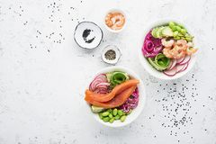 Fresh seafood recipe. Shrimp salmon poke bowl with fresh prawn, brown rice, cucumber, pickled sweet onion, radish, soy. Beans edamame portioned with black and Royalty Free Stock Photography