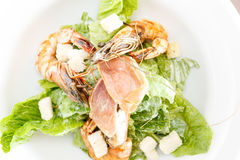Fresh seafood salad with shrimps. Closeup overhead view of a serving of fresh seafood salad with shrimps, fish and feta cheese served on green lettuce leaves stock photo