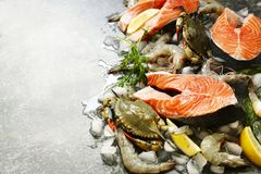 Fresh seafood: salmon steak, crabs and shrimps on stone background. With copy space Stock Image