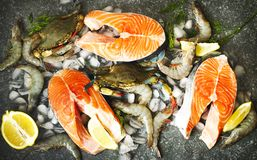 Fresh seafood: salmon steak, crabs and shrimps on stone background,. Top view Royalty Free Stock Image