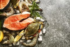 Fresh seafood: salmon steak, shrimps and crabs on stone background. With copy space Royalty Free Stock Photography